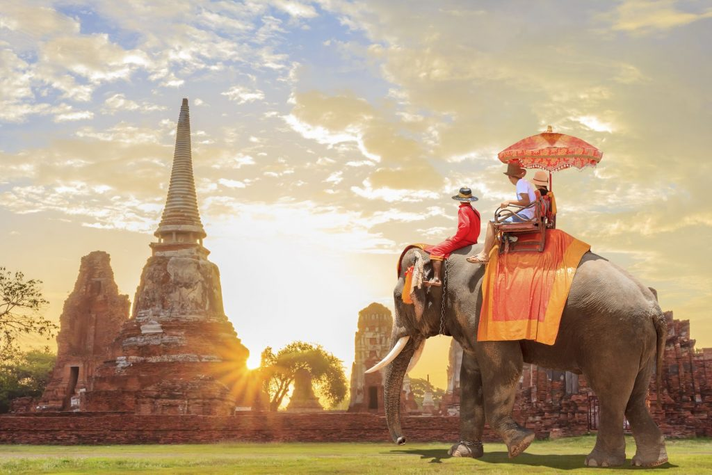 Tourists on an ride elephant tour of the ancient city in sunrise background, Cambodia